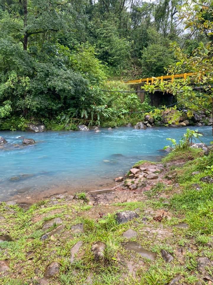 Blue waterfall in Tenorio, Costa Rica with a suspension bridge overhead
