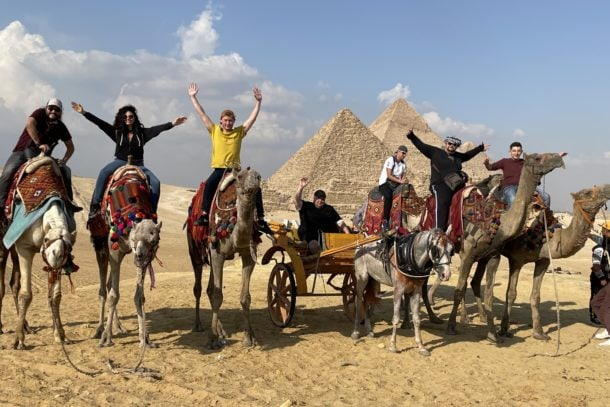 In front of the Great Pyramids of Giza on camels
