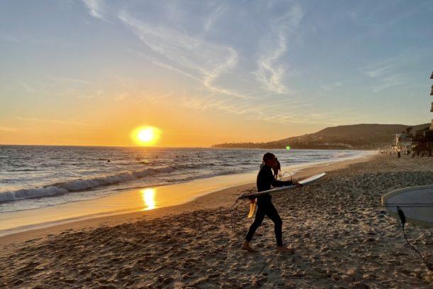 a surfer leaving laguna beach, california at sunset