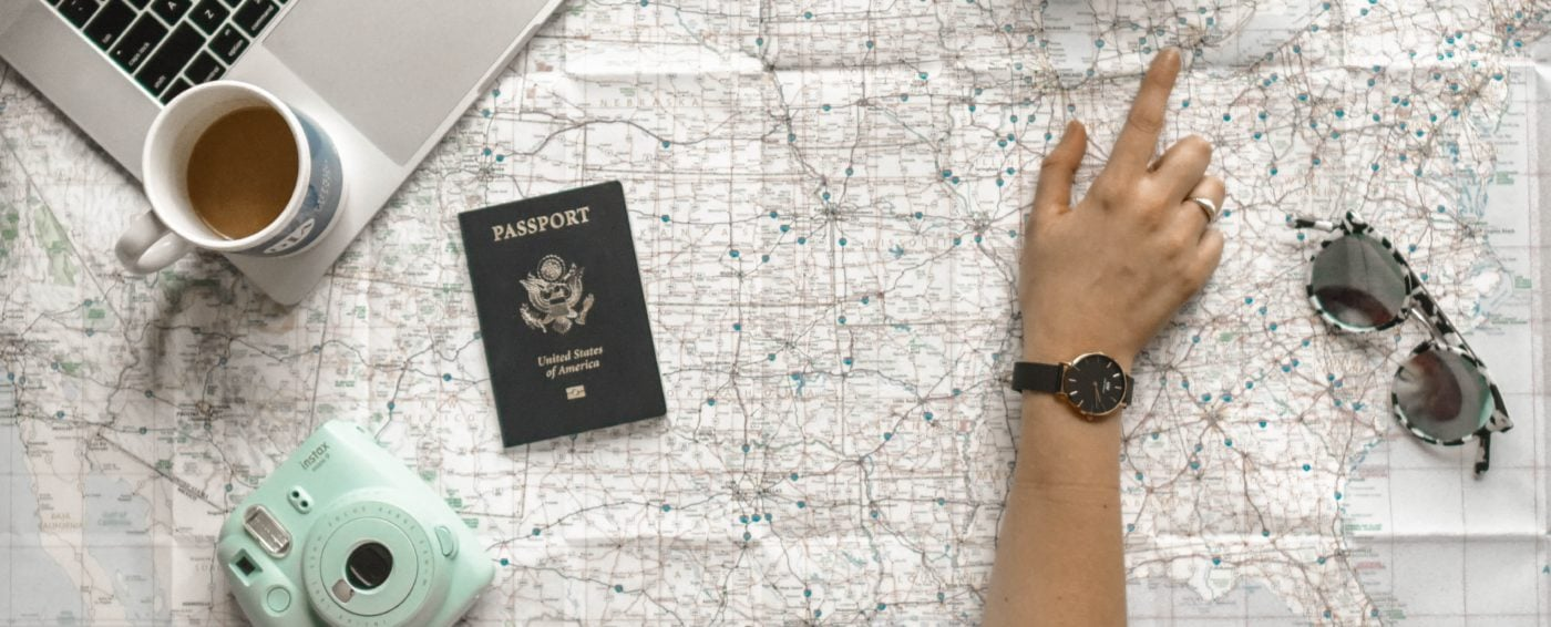 Planning a trip with camera, passport, laptop, and map laid out on table