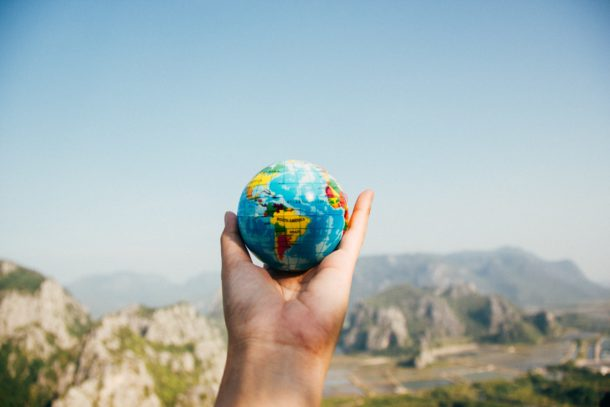 Holding up a small globe over beautiful landscape