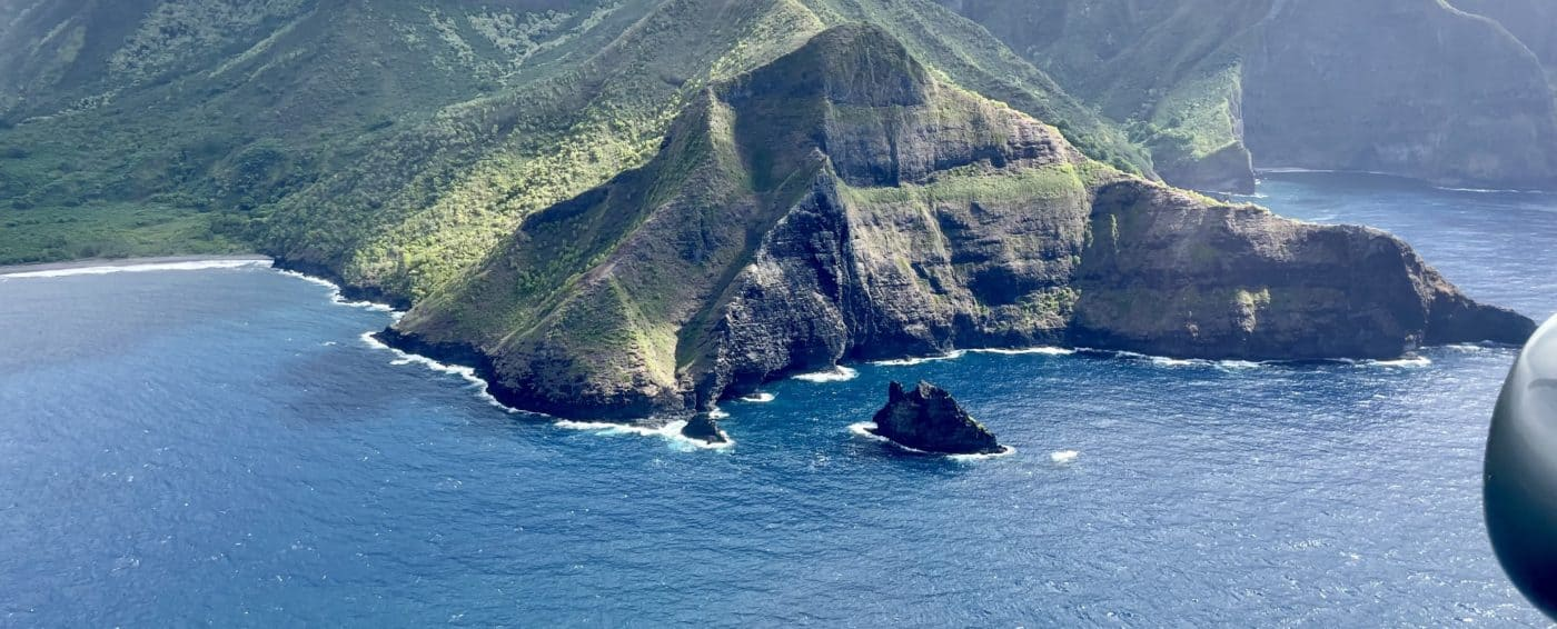 Aerial view of green island surrounded by blue ocean water