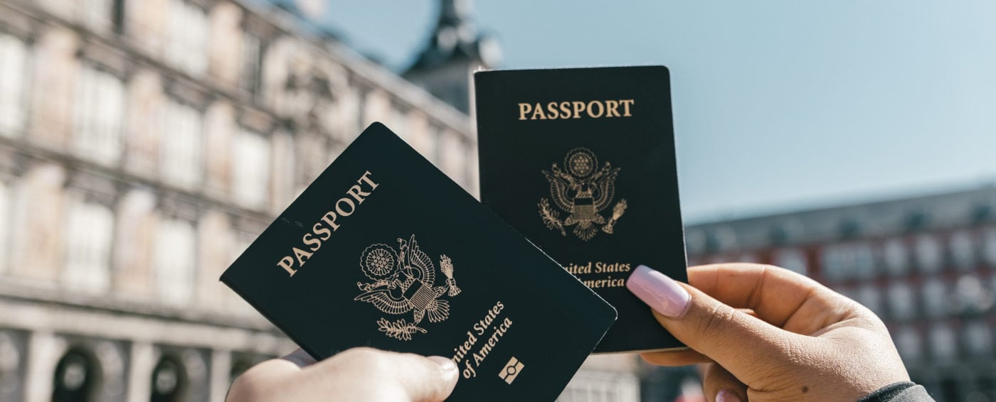 Couple holding up their passports in front of a building